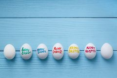 Easter eggs with color titles `Happy Easter` written by paint brush are on the blue colored wooden background. Easter eggs with color titles `Happy Easter` Stock Images