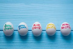 Easter eggs with color titles Happy Easter written by paint brush are on the blue colored wooden background. Easter eggs with color titles Happy Easter written Royalty Free Stock Photo