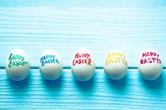 Easter eggs with color titles `Happy Easter` written by paint brush are on the blue colored wooden background.  Royalty Free Stock Images
