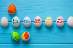 Easter eggs with color titles Happy Easter written by paint brush are on the blue colored wooden background.  Royalty Free Stock Images