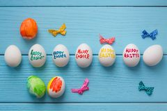 Easter eggs with color titles Happy Easter written by paint brush and small bows  are on the blue colored woode. N background Stock Image