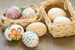 Easter eggs. Colored drawings on Easter eggs. Easter eggs in a 2 wicker basket on the tablecloth of burlap royalty free stock photo