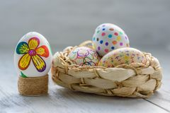 Easter eggs. Colored drawings on Easter eggs. Easter eggs in a wicker basket on a wooden table stock photography