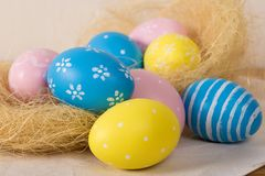 Easter eggs with colored eggs in nest royalty free stock photos