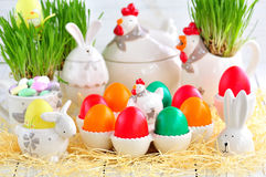 Easter eggs colored with organic paints and plate in the form of chickens and rabbits on a white wooden background. Stock Images