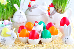 Easter eggs colored with organic paints and plate in the form of chickens and rabbits on a white wooden background. Royalty Free Stock Images