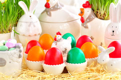 Easter eggs colored with organic paints and plate in the form of chickens and rabbits on a white wooden background. Stock Photos