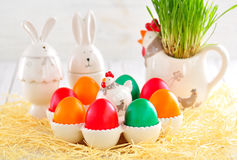 Easter eggs colored with organic paints and plate in the form of chickens and rabbits on a white wooden background. Stock Photography