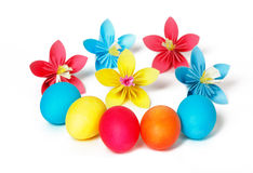 Easter eggs and colored paper flowers Stock Photos