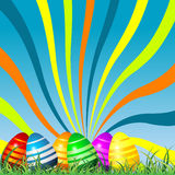 Easter eggs colorful background. Easter eggs on grass over colorful sky background Stock Photography