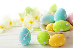 Easter eggs. Colorful easter eggs in bowl and spring flowers