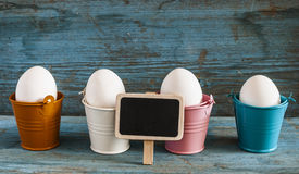 Easter eggs in colorful buckets Royalty Free Stock Images