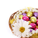 Easter eggs, colorful chocolate eggs with chamomile flower and pearl necklaces in basket Stock Photography