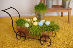 Easter eggs and colorful decor trolley in studio Royalty Free Stock Photo