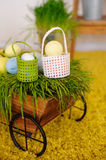 Easter eggs and colorful decor trolley in studio Royalty Free Stock Images