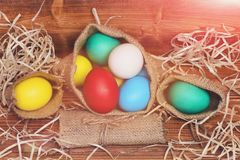 Painted easter colorful eggs in burlap sack on wooden background Royalty Free Stock Photography