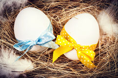 Easter eggs with colorful ribbons in a nest closeup Stock Photos