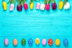 Easter eggs with colorful tulips on wooden background, easter holiday concept. Copy space for text. royalty free stock photo