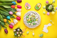 Easter eggs with colorful tulips on yellow background.Easter holiday concept. Easter decor. stock photography