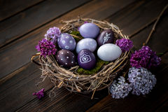 Easter eggs. Colorful Easter eggs on a wooden table with lilac Royalty Free Stock Photos