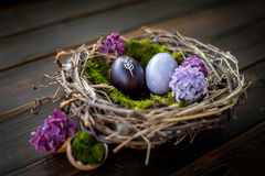 Easter eggs. Colorful Easter eggs on a wooden table with lilac and moss Royalty Free Stock Photography