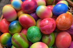 Easter eggs in a basket. Easter eggs coloured in many colours and patters collected in a basket Stock Photos