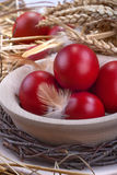 Easter eggs. Colourful traditionally painted Easter eggs in a wooden bowl and in the straw Royalty Free Stock Image