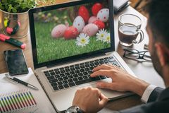 Easter eggs on a computer screen. Man working in his office. View from above royalty free stock images