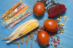 Easter eggs, corn and decorations on a blue wooden background. Royalty Free Stock Images