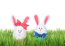 Easter Eggs crafted into bunnies sitting in grass. Easter Eggs crafted into bunnies, boy and girl, wearing bow tie and bow on ear sitting in green grass isolated royalty free stock photo
