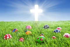 Easter eggs and Cross on grass. Picture of colorful easter eggs laying on the grass with a bright Cross Stock Photos