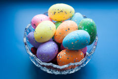Easter eggs in a crystal dish on a blue background, Royalty Free Stock Photos
