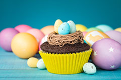 Easter Eggs and Cupcake. Colorful Easter Eggs and cupcake with nest on a blue background Royalty Free Stock Image