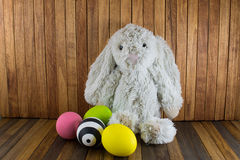 Easter eggs and cute plush Bunny on wood background Royalty Free Stock Photos