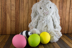 Easter eggs and cute plush Bunny on wood background Royalty Free Stock Image