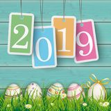 Easter Eggs Cyan Wood Pastel Price Stickers 2019. Price stickers 2019 on the wooden background with easter eggs in the grass Royalty Free Stock Photography