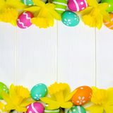 Easter eggs and daffodils double border over white wood Stock Photography