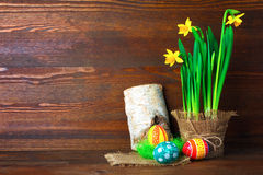 Easter eggs. Daffodils in the flowerpot near to the grass with Easter eggs on wooden background stock photos