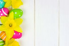 Easter eggs and daffodils side border over white wood Stock Images