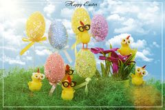 Easter eggs decorated with colorful dots. Small yellow chickens. Easter eggs decorated with colorful dots. Little yellow Chicks play in the grass royalty free stock photo
