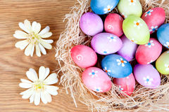 Easter eggs decorated with daisies on a nest of straw Royalty Free Stock Photography