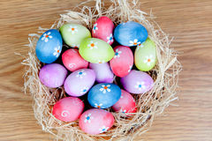 Easter eggs decorated with daisies on a nest of straw Stock Photos