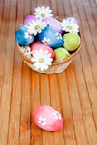 Easter eggs decorated with daisies tucked in a basket Stock Photography