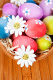 Easter eggs decorated with daisies tucked in a basket Stock Photos