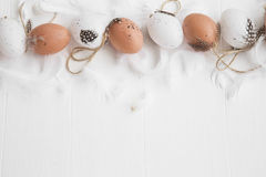 Easter eggs decorated with feathers on white painted wooden back Royalty Free Stock Images