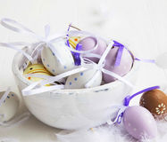 Easter eggs decorated with feathers on white wooden bowl Stock Photos