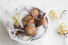 Easter eggs decorated with feathers on white wooden bowl Stock Photo