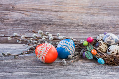 Easter eggs decorated with lace, pussy-willow  and quail eggs in small nest on wooden background Royalty Free Stock Photos