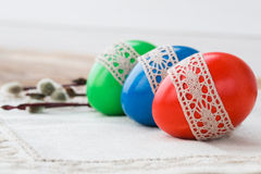 Easter eggs decorated with lace on white tablecloth. Copy space, selective focus Stock Image