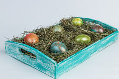 Easter eggs. Decorated eggs for Easter in a nest of hay on a decorated wooden tray on white background Royalty Free Stock Photo